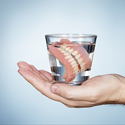 Hand holding full dentures in a glass of water
