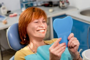 Senior woman checking smile after treatment for gingivitis