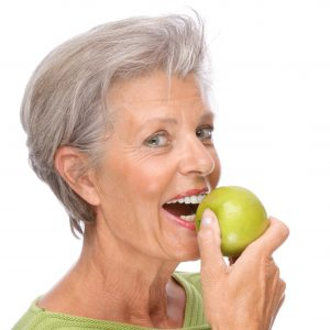 woman holding an apple smiling