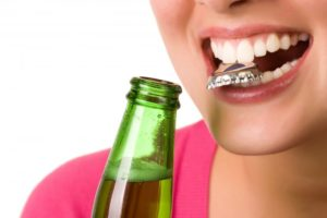 close up woman using her teeth to open a bottle