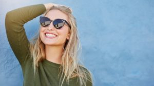 woman in sunglasses enjoying the results of her teeth whitening in summer