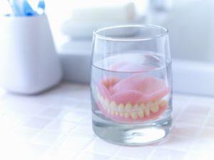 dentures soaking in glass of water